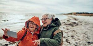 senior women laughing taking photo on the beach