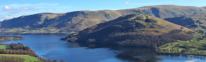A view of the Northern end of Ullswater, rolling hills and blue water