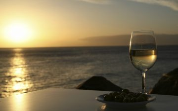 A glass of white wine over looking the sun setting over the sea.