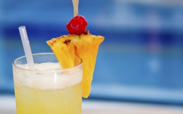 Close up of a tropical cocktail on a blue background