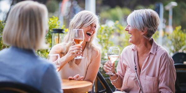 group of senior friends drinking wine