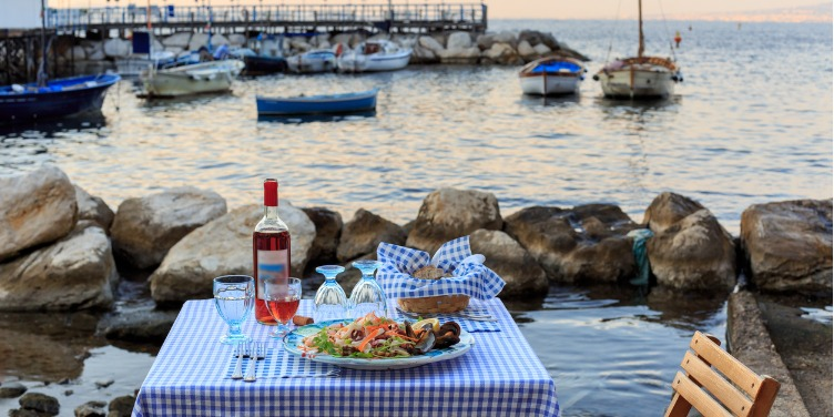 an image of a dinner table for two by the sea harbour in Sorrento, Italy