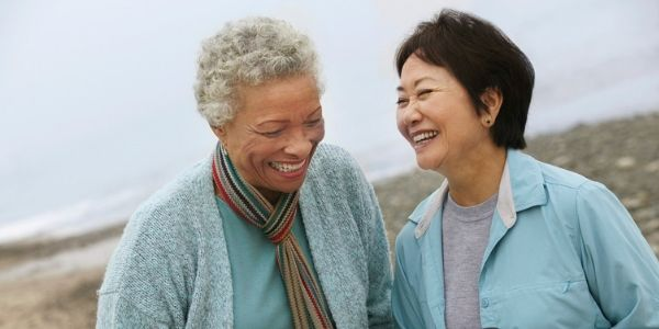 senior female friends laughing on the beach