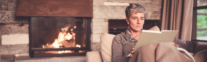 Mature woman keeping warm while reading a book
