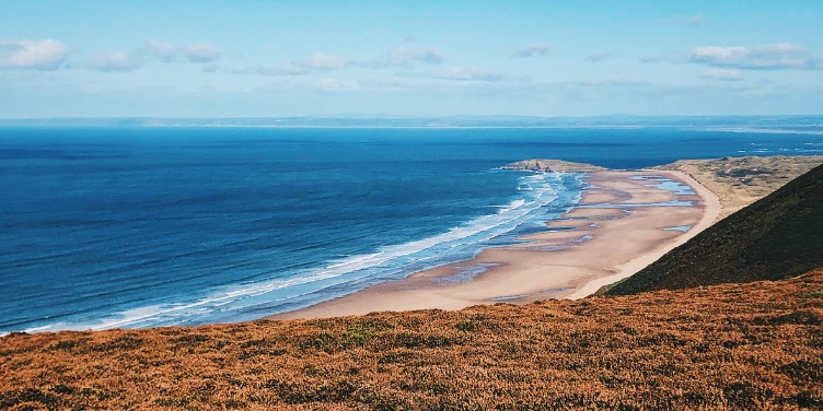 an image of Rhossili beach from the clifftop