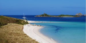 an image of a yacht and the white-sandy beach in Tresco, Isles of Scilly