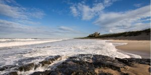 an image of the waves at Bamburgh Beach, with Bamburgh Castle in the distance