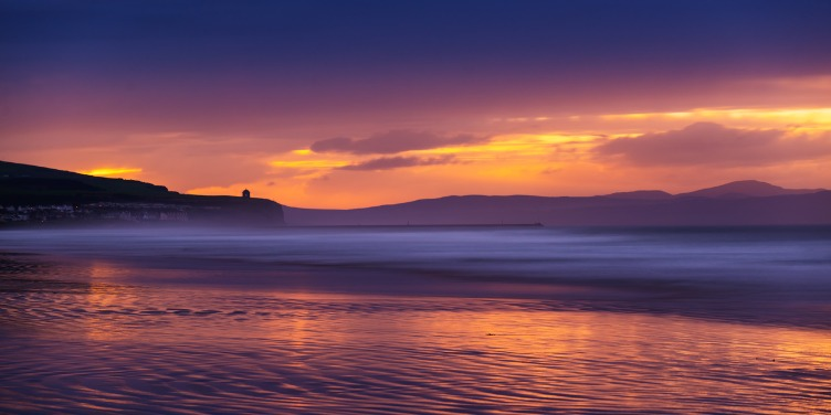 an image of the water at Portstewart Strand at sunset with the temple in the distance