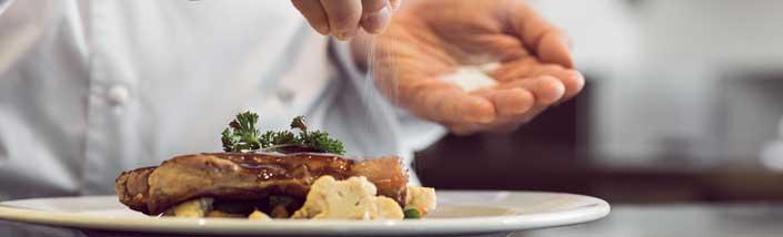 Chef putting salt on meat