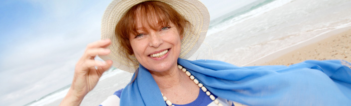 Close up of woman in blue and white, smiling on the beach