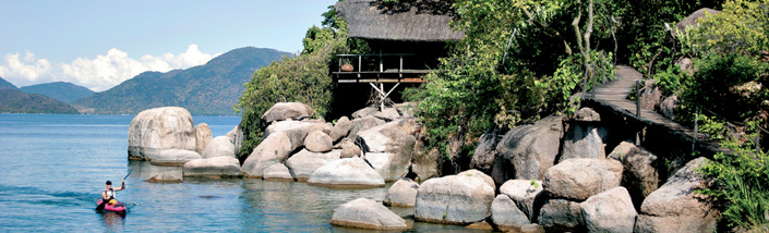 Person canoeing outside a lake house in malawi