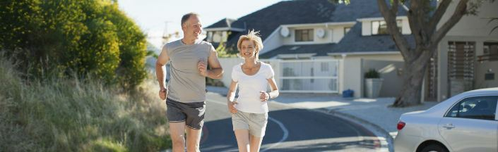 An older couple going on a run on a sunny day