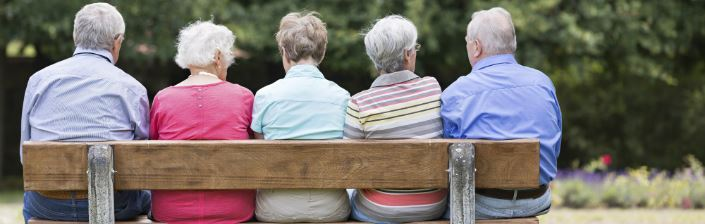 A group of older adults sitting on park bench