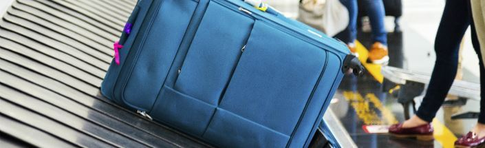 Navy blue personal baggage on a conveyor belt