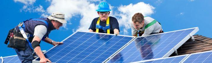 Three men installing solar panels