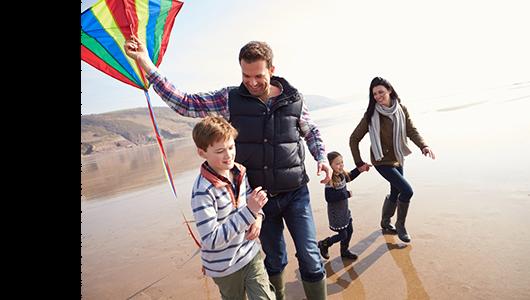 Family on beach wityh kite