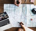 Travel planning with camera laptop and map