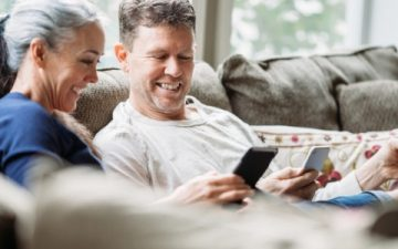 Mature couple sat on sofa smiling with phones
