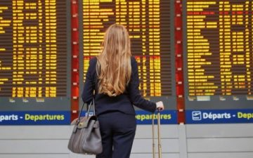 woman looking at departure boards in airport