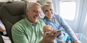 senio couple using mobile phone on airplane