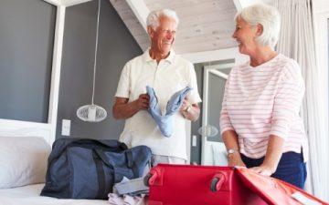 senior couple smiling while packing suitcase