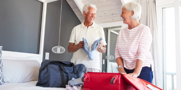 senior couple smiling while packing suitcase