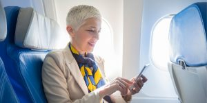 older woman on airplane with phone