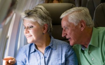 older couple looking out of window of airplane
