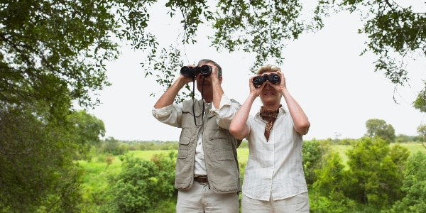 senior couple looking at landscape with binoculars