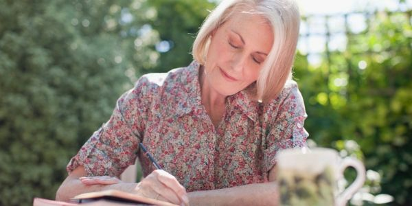 senior woman writing outdoors