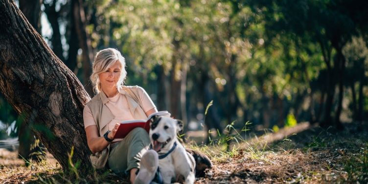 senior woman reading outdoors with dog