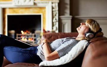 woman relaxing on sofa with headphones