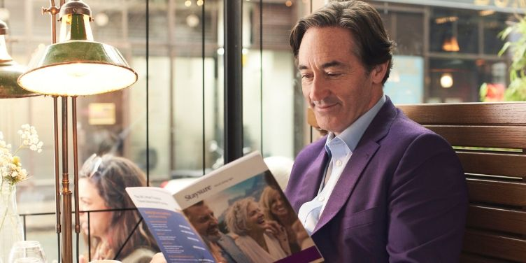 man smiling while reading Staysure policy book