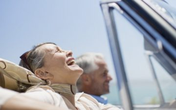 Silver Migration: Happy Mature Travellers Driving In Car