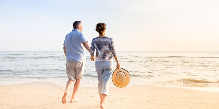 mature couple walking on the beach together