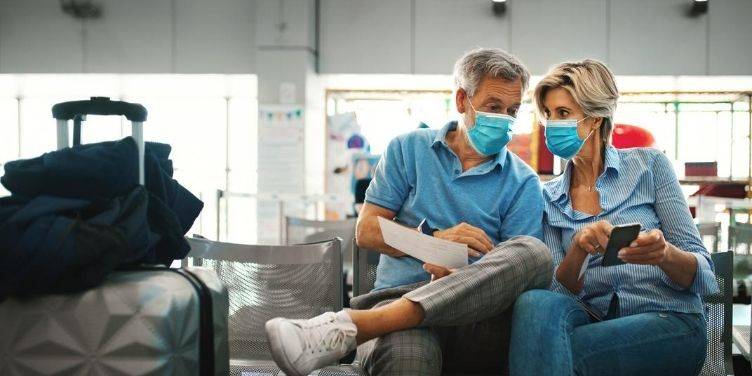 Senior couple waiting at airport wearing face masks