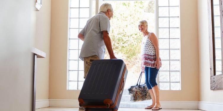 Senior couple leaving for holiday with luggage
