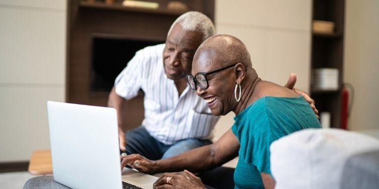senior couple smiling looking at laptop