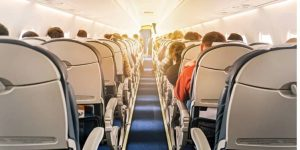 Aircraft cabin with rows of seats, view down aisle
