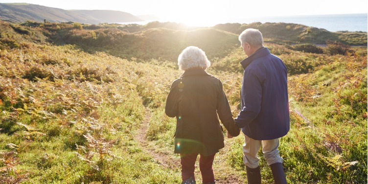 an image of a couple walking along a coastal path towards the flaring sun