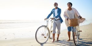 an image of a smiling couple walking two bicycles along the beach
