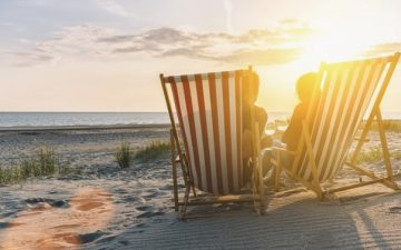 Couple on beach chairs at sunset