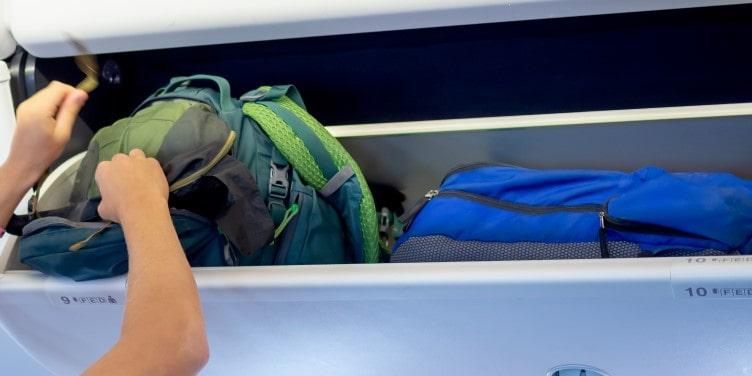 Passenger putting hand luggage in locker