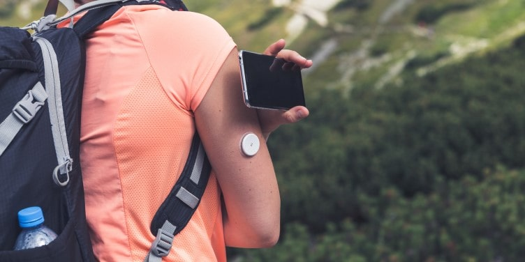 Person checking glucose levels with flash glucose monitor