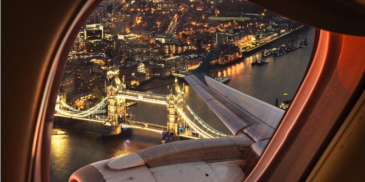 an image of Tower Bridge in London at night from the view of a plane window