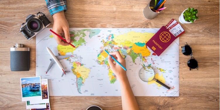 an image of a couple planning their holiday on a map, with various items like passports and cameras