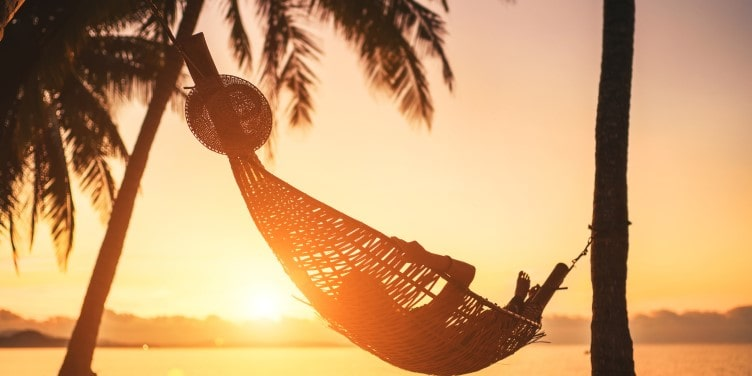 Hammock between palm trees on sandy beach at sunset