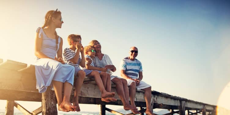 Multi-generational family sitting on a pier on holiday