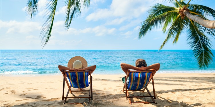 Couple relaxing on deck chairs at the beach