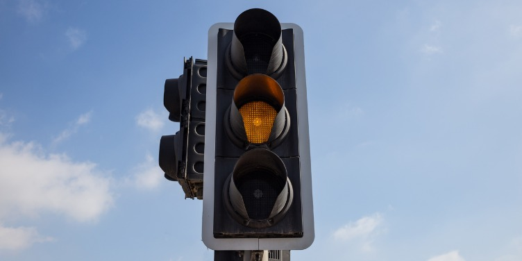an image of a traffic light on amber with a blue sky in the background